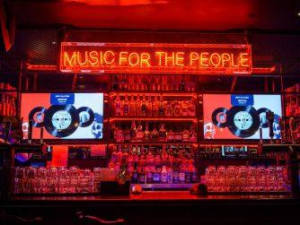 Über einem Tresen in einer Bar hängt die Leuchtschrift: Music for the People