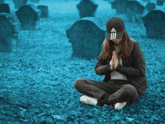Mädchen mit Adidas-Mütze sitzt auf einem Friedhof und betet.